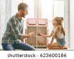 Small photo of Happy father and daughter girl play with doll house at home. Funny lovely family is having fun in kids room.