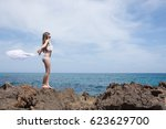 young girl on the rocky coast... | Shutterstock . vector #623629700