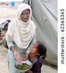 Small photo of KARACHI, PAKISTAN, OCT 03: Flood affectee woman hold her food pot as she is protesting against providing of allegedly substandard food, at relief camp established at Hawks Bay area on October 3, 2010 in Karachi, Pakistan.
