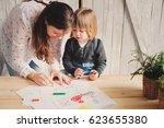 mother teaching toddler boy to... | Shutterstock . vector #623655380