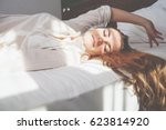 pretty young woman on bed in... | Shutterstock . vector #623814920