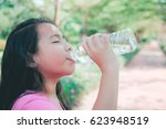 little girl drinking water in... | Shutterstock . vector #623948519