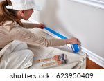 woman painting wall   Shutterstock . vector #623950409