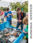 Small photo of Auckland, New Zealand - April 09, 2017: Man and kids searching in many parts of thrown away as e-waste at EcoDay in New Lynn.