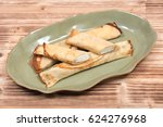 Small photo of Delicious cheese blintz on green plate and wooden vintage tray
