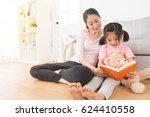 Small photo of asian young woman accompany children reading comic book in the afternoon of the holiday at home in the living room and lovely girl holding her teddy bear sitting on the floor to earnestly study.