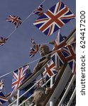Small photo of On board P&O Cruises MV Oriana, July 23, 2015: Portrait view of a number of men and women at a deck party waving British flags. More flags are seen on bunting against the background of a blue sky