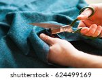 Small photo of Tailor. Man Hands notch tailor tailor's scissors cloth. Close Up.