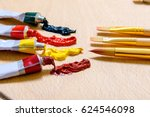 Small photo of Open tubes, full of bright paint are afore handy brushes at wooden desk. Focus on equipment. Close-up