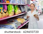 Stock photo friendly girl seller showing different types of food for pets in pet shop 624653720
