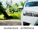 Stock photo front of white car on street with tree background 624805616