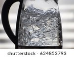 Horizontal closeup of water boiling in a glass vessel, with a light gray background with horizontal out-of-focus bands.