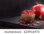 Ripe pomegranate fruit on a old  black wooden vintage background. - stock photo