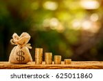 Small photo of Money bag and stacking gold coins in the public park, saving money for loan with working capital management concept.