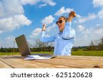 Small photo of A women with a laptop, sitting in the garden and make a great deal, she happy with her arms up