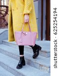 Small photo of Fashionable young woman in yellow coat with rose handbag in hand . Street style .