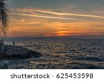 Small photo of The sunset at Kusadasi, Turkey over the Mycale Strait towards the Greek island of Samos