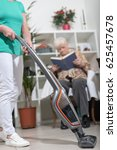 Small photo of Home helper vacuuming for elderly woman