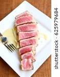 Small photo of aerial view of seared sashimi Ahi tuna with pear sauce as an appetizer tapa at a fine dining restaurant