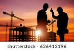 Commercial Construction Concept with Silhouette of Two Workers Wearing Hard Hats and Construction Site in the Background. - stock photo