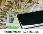 Small photo of One checkbook on a 1040 tax form, a tax refund check and a variety of cash paper money. A tax refund check with paper money, a checkbook and a 1040 tax form.