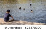 Boy Sitting Beside Pond