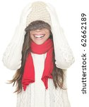 Playful cute winter woman in sweater and hat having fun laughing with winter knit hat pulled down over the eyes. Cute asian girl isolated on white background. - stock photo