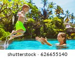 Small photo of Happy child in action - active kid swim with fun in swimming pool. Baby son jump high to mother catching hands. Healthy family lifestyle, summer vacation water sports activity and lesson with parents