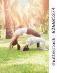 mom and child yoga in the park | Shutterstock . vector #626685374