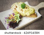 Small photo of Delicious egg benedict on bake paper with salad above board, isolated on wooden background