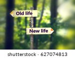 Stock photo signpost in a park with arrows old and new life pointing in two opposite directions 627074813