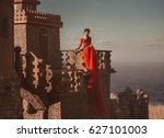 Small photo of Beautiful girl sitting on the balcony of the castle. The princess has a red dress with a long train. The backdrop of the sky and the sea.