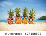 Stock photo family of funny attractive pineapples in stylish sunglasses on the sand against turquoise sea 627188573