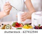 woman preparing tasty yogurt at ... | Shutterstock . vector #627412544