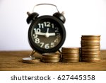 Small photo of Rows coin in fount of alarm clock for business concept,finance,tax time.