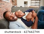 father and son cuddling on sofa ... | Shutterstock . vector #627662744