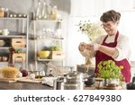 happy senior woman cooking in... | Shutterstock . vector #627849380