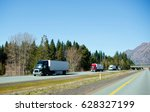 Small photo of The chain of modern colorful semi trucks of different models and manufacturers with trailers moving cargo one after the other on the flat straight interstate highway with trees in sunny California.