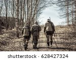 Small photo of Group of men hunters going up on rural road during hunting season