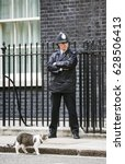 Small photo of LONDON, UK - Apr 19, 2017: Metropolitan police officer on duty and the cat named Larry the 10 Downing Street cat and Chief Mouser to the Cabinet Office. Larry is a brown and white tabby.