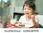 happy little asian girl eating... | Shutterstock . vector #628638998