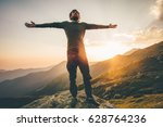 Traveler Man raised hands at sunset mountains Travel Lifestyle emotional concept adventure summer vacations outdoor hiking mountaineering harmony with nature - stock photo