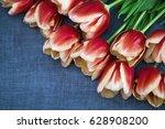 Red Tulips Lying On A Dark Blu...