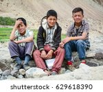 Small photo of Leh, India - Jul 18, 2015. Tibetan boys sitting on road in Nubra Valley, India. 65% of children attend school, but absenteeism of both students and teachers remains high.