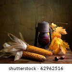 Still Life Autumn concept image with corn and maple leafs - stock photo