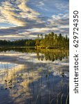 Small photo of Bright summer sunset over the lake in the woods, Sweden around town Dorotea