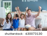 smiling family cheering while... | Shutterstock . vector #630073130
