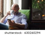 a man drinks coffee and checks... | Shutterstock . vector #630260294