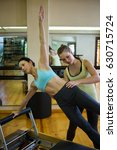 Small photo of Female trainer assisting woman with stretching exercise on reformer in gym