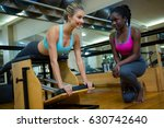 smiling trainer assisting woman ... | Shutterstock . vector #630742640